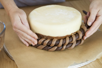 Twists of icing being put around cake to give basket effect