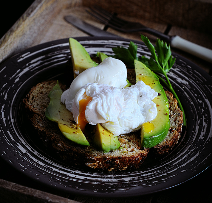 soft poached egg served on sliced avocado on brown bread