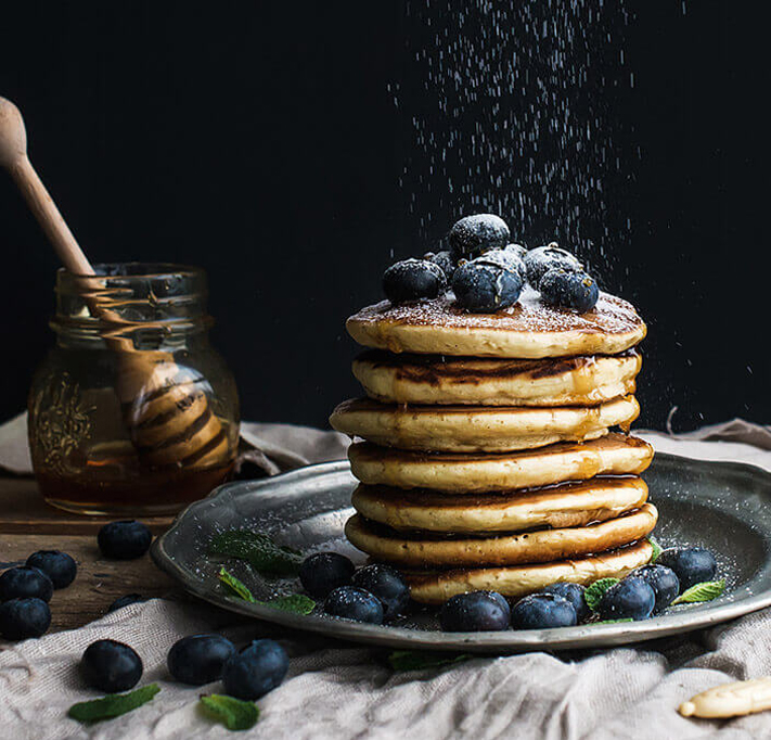 stack of pancakes with blueberries, honey and icing sugar