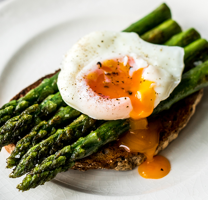 running poached egg on asparagus and brown toast